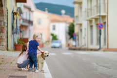 Two cute little sisters and a dog outdoors Royalty Free Stock Photos