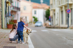 Two cute little sisters and a dog outdoors Royalty Free Stock Images