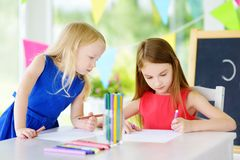 Two cute little sisters drawing with colorful pencils at a daycare Stock Image