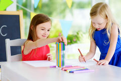 Two cute little sisters drawing with colorful pencils at a daycare. Creative kids painting together. Stock Photography
