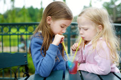 Two cute little sisters drinking frozen slushie drink royalty free stock photos