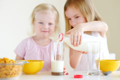Two cute little sisters eating cereal in a kitchen Stock Image