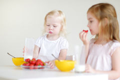 Two cute little sisters eating cereal in a kitchen Stock Photos