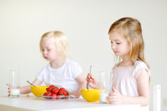 Two cute little sisters eating cereal in a kitchen Royalty Free Stock Photography