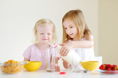 Two cute little sisters eating cereal in a kitchen Stock Images