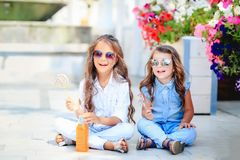 A Two cute little sisters eating huge lollipops outdoors on beautiful summer day. royalty free stock images