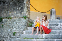 Two cute little sisters eating ice-cream while sitting on the stairs on summer day Royalty Free Stock Photography