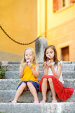 Two cute little sisters eating ice-cream while sitting on the stairs on summer day Royalty Free Stock Image