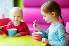 Two cute little sisters eating ice cream together Royalty Free Stock Photos
