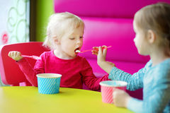 Two cute little sisters eating ice cream together Royalty Free Stock Photography