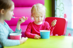 Two cute little sisters eating ice cream together Royalty Free Stock Photo