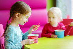 Two cute little sisters eating ice cream together Royalty Free Stock Image