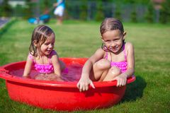 Two cute little sisters frolicing and splashing in Royalty Free Stock Photo