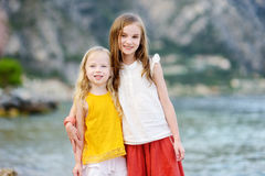 Two cute little sisters having fun on a beach of Limone sul Garda, a small town and comune in the province of Brescia, Italy. Two cute little sisters having fun Stock Photo