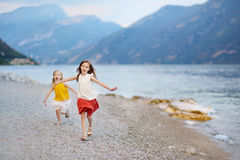 Two cute little sisters having fun on a beach of Limone sul Garda, a small town and comune in the province of Brescia, Italy. Two cute little sisters having fun Royalty Free Stock Photography