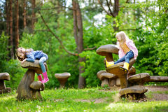 Two cute little sisters having fun on giant wooden mushrooms stock photos