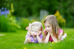 Two cute little sisters having fun on the grass Royalty Free Stock Photos