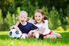 Two cute little sisters having fun playing a soccer game Stock Photos