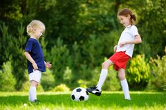 Two cute little sisters having fun playing a soccer game Stock Photo