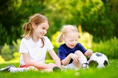 Two cute little sisters having fun playing a soccer game Stock Image