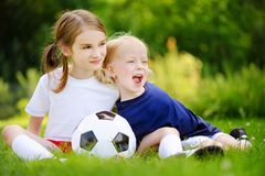 Two cute little sisters having fun playing a soccer game Royalty Free Stock Photography