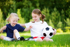 Two cute little sisters having fun playing a soccer game on sunny summer day. Sport activities for children. Royalty Free Stock Photo