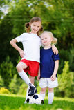 Two cute little sisters having fun playing a soccer game on sunny summer day. Sport activities for children. Stock Photography