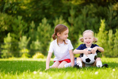 Two cute little sisters having fun playing a soccer game on sunny summer day. Sport activities for children. Stock Photo