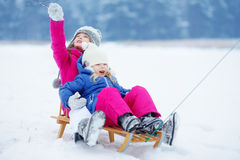 Two cute little sisters having fun with a sleight in winter park Royalty Free Stock Image