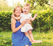 Two cute little sisters having fun on a swing together in beauti Royalty Free Stock Photo