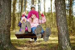 Two cute little sisters having fun on a swing together in beautiful autumn forest on warm and sunny day outdoors Stock Image
