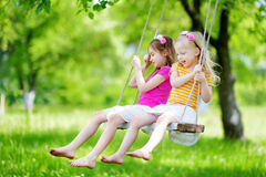 Two cute little sisters having fun on a swing together in beautiful summer garden Royalty Free Stock Photos