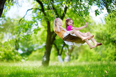 Two cute little sisters having fun on a swing together in beautiful summer garden. On warm and sunny day outdoors Royalty Free Stock Images