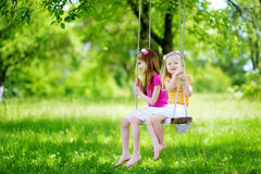 Two cute little sisters having fun on a swing together in beautiful summer garden Stock Photography