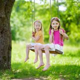 Two cute little sisters having fun on a swing together in beautiful summer garden Stock Photos