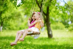 Two cute little sisters having fun on a swing together in beautiful summer garden on warm and sunny day outdoors. Active summer leisure for kids Royalty Free Stock Photography