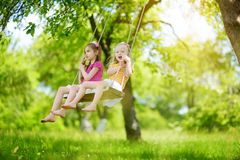 Two cute little sisters having fun on a swing together in beautiful summer garden on warm and sunny day outdoors. Active summer leisure for kids Stock Photos