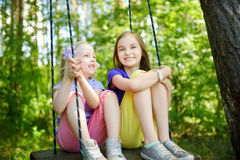 Two cute little sisters having fun on a swing together in beautiful summer garden on warm and sunny day Stock Photo