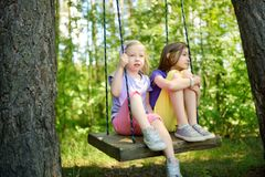 Two cute little sisters having fun on a swing together in beautiful summer garden on warm and sunny day outdoors. Summer outdoor leisure for kids Stock Photo