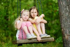 Two cute little sisters having fun on a swing together in beautiful summer garden on warm and sunny day outdoors. Summer outdoor leisure for kids Royalty Free Stock Photos