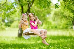 Two cute little sisters having fun on a swing together in beautiful summer garden on warm and sunny day outdoors. Active summer leisure for kids Stock Photo