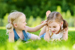 Two cute little sisters having fun together on the grass on summer day Royalty Free Stock Images