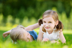 Two cute little sisters having fun together on the grass on summer day Stock Photos