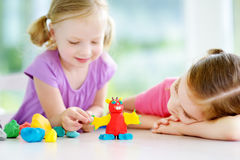Two cute little sisters having fun together with modeling clay at a daycare. Creative kids molding at home. Children play with pla. Two cute little sisters Stock Photos