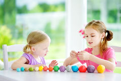 Two cute little sisters having fun together with modeling clay at a daycare. Creative kids molding at home. Children play with pla Royalty Free Stock Images