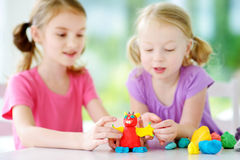 Two cute little sisters having fun together with modeling clay at a daycare. Creative kids molding at home. Children play with pla. Two cute little sisters Royalty Free Stock Image