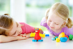 Two cute little sisters having fun together with modeling clay at a daycare. Creative kids molding at home. Children play with pla Royalty Free Stock Image
