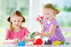 Two cute little sisters having fun together with modeling clay at a daycare. Creative kids molding at home. Children play with pla Royalty Free Stock Photo