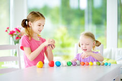 Two cute little sisters having fun together with modeling clay at a daycare. Creative kids molding at home. Children play with pla Stock Image