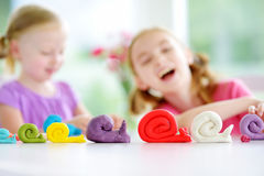 Two cute little sisters having fun together with modeling clay at a daycare. Creative kids molding at home. Children play with pla Stock Photo